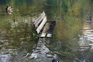Eine Parkbank unter Wasser nach heftigem Regen.