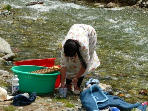 A Berber woman washes her laundry at the river. They do not have a laundry machine.